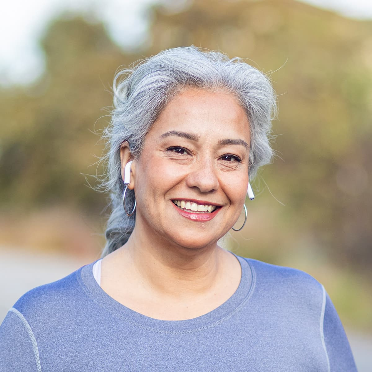 Woman with silver hair smiling while wearing airpods