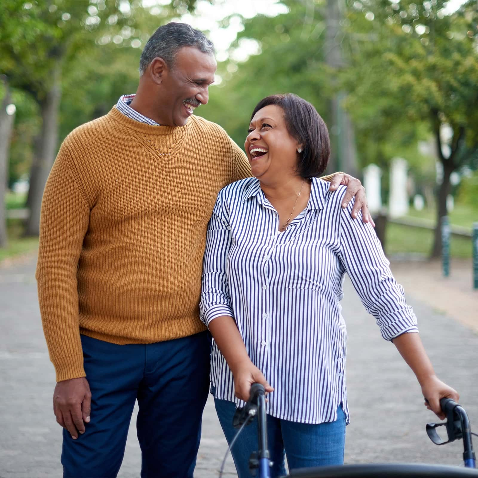 happy mature woman using a walker while in the park with her smiling mature husband