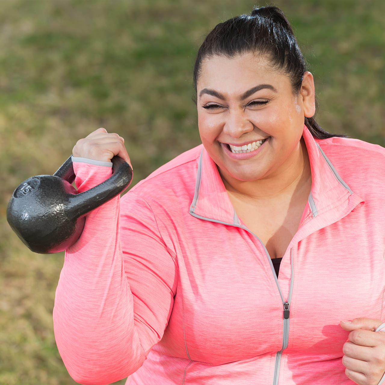 Hispanic woman exercising to lose weight with kettlebell